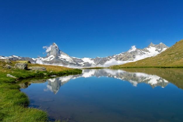 Il bellissimo paesaggio delle alpi svizzere con il lago stellisee e il riflesso della montagna del cervino nell'acqua