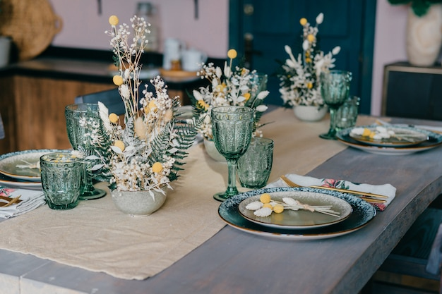 Bellissimo tavolo realizzato con piatti, bicchieri e fiori.
