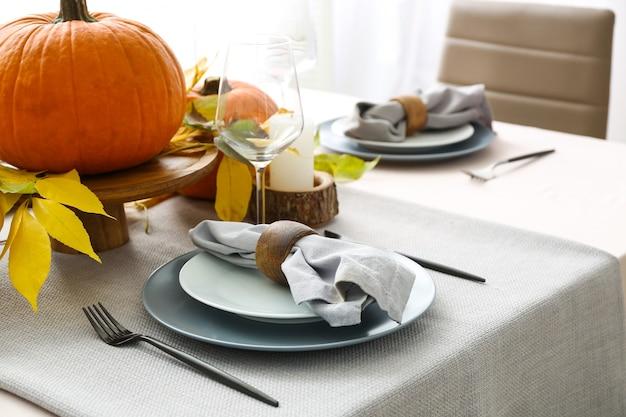 Bella tavola con zucche e foglie d'autunno nella sala da pranzo