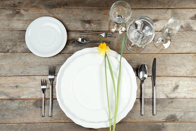 Bella tavola apparecchiata con piatti bianchi su tavola di legno