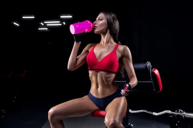 Bello atleta alto si siede su una panchina e beve da uno shaker.