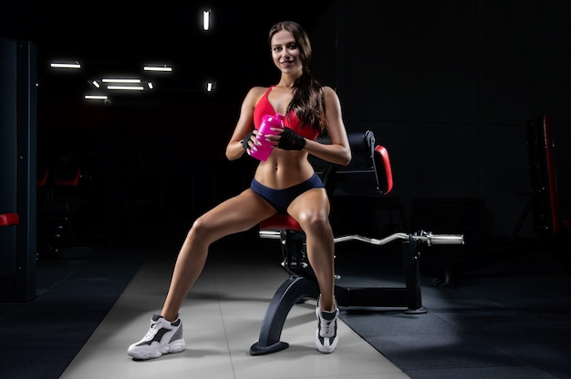 Bella sportiva alta si siede su una panchina con uno shaker in mano e sorride. bodybuilding e concetto di nutrizione sportiva.
