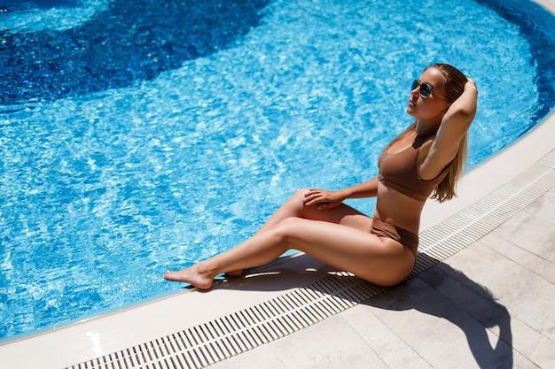 Una bellissima modella abbronzata si rilassa a bordo piscina. giovane donna sexy in costume da bagno beige in una giornata di sole estivo a bordo piscina