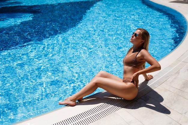 La bella donna abbronzata si sta rilassando in piscina. ragazza sexy in costume da bagno beige in una giornata di sole estivo a bordo piscina