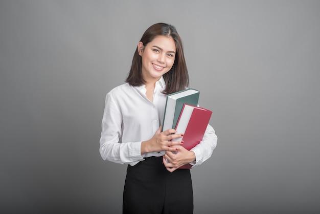 Bella insegnante donna che tiene il libro su sfondo grigio