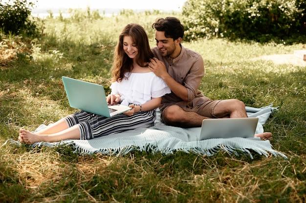 Bella coppia teen uomo e donna che lavorano utilizzando il computer portatile per lavorare in vacanza parco all'aperto