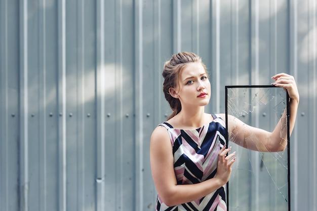 Bella ragazza teenager che tiene il vetro rotto nelle sue mani. concetto per superare le sfide nell'adolescenza.