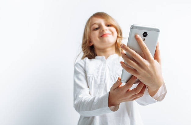 Bella ragazza teenager che esamina il telefono, parlando sul video