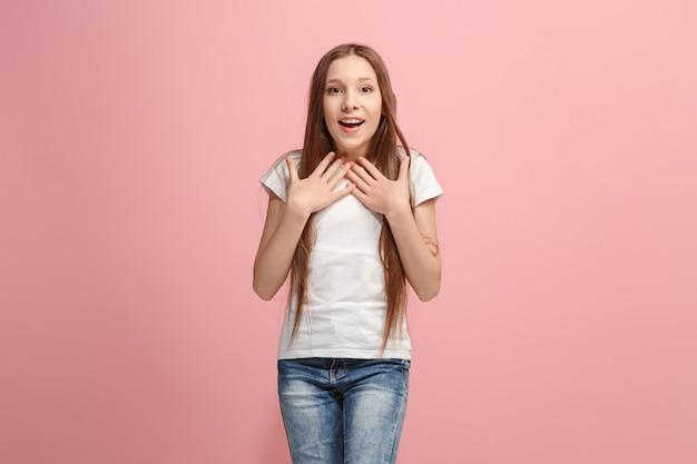 Bella ragazza teenager che sembra sorpresa isolata sulla parete rosa