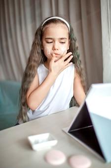 Bella ragazza adolescente guardando master class di bellezza con tablet online e facendo la procedura termale da sola, bambino con maschera liscia sul viso, salone di bellezza a casa