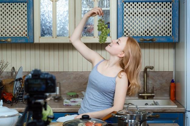 Una bella ragazza adolescente con i capelli rossi dà alcuni suggerimenti per un'alimentazione sana nel suo video blog a casa.