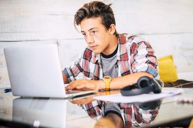 Bellissimo adolescente concentrato per i suoi studi facendo i compiti a casa sul tavolo con laptop o computer - cuffie sul tavolo - concetto di stile di vita indor - ragazzo che scrive e legge