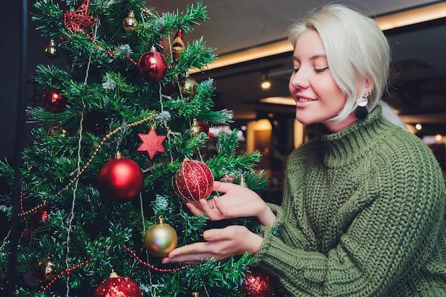 Bella ragazza dell'adolescente che decora l'albero di natale.
