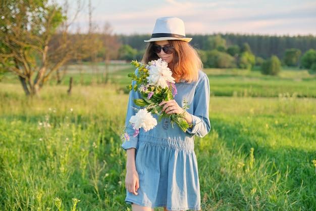 Bella ragazza adolescente in jeans vestito cappello con bouquet di fiori di campo, paesaggio scenico dello spazio, bellezza, natura, spazio di copia