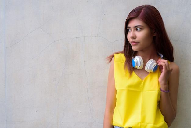 Bella ragazza dell'adolescente che porta camicia gialla vibrante