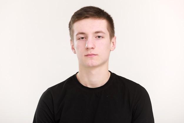 Un bell'uomo adolescente con una faccia seria triste, capelli scuri e una maglietta nera con le mani giunte su uno sfondo bianco. mock up, modello per la stampa di design.