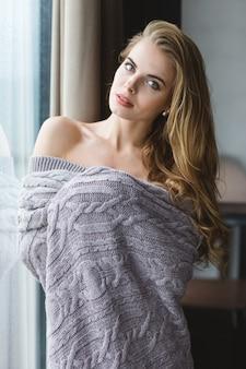 Bella giovane donna allettante con i capelli lunghi in piedi vicino alla finestra in coperta lavorata a maglia