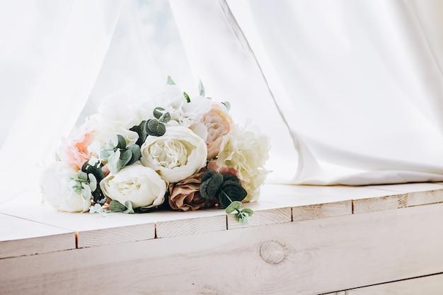 Bellissimo bouquet tenero di fiori bianchi sulla scrivania in legno con tessuto bianco sulla superficie.