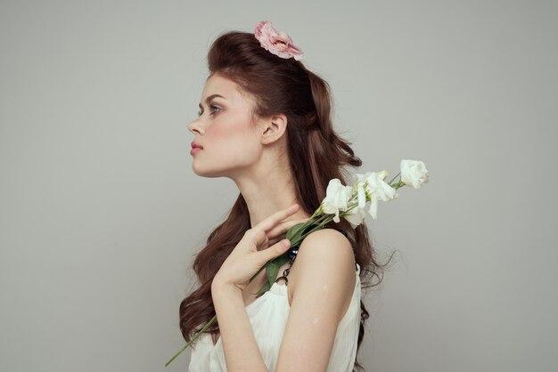 Bella donna tenera primavera con fiori al tavolo