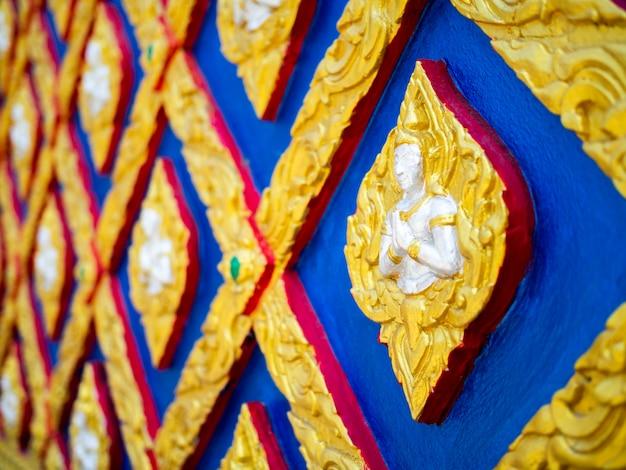 Bello fondo della parete dello stucco di arte tailandese. primo piano in stile tailandese del motivo a stucco in bassorilievo.