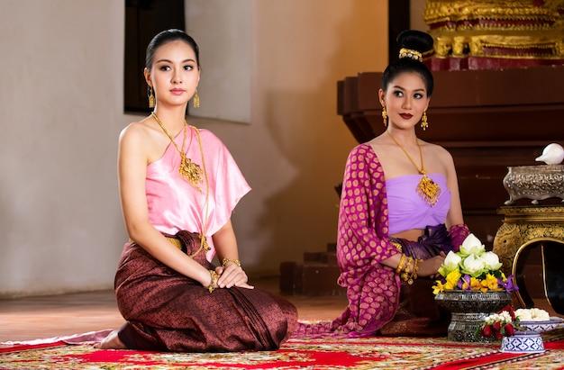 Bella ragazza tailandese in costume tradizionale rosa del vestito della tailandia al posto tailandese del tempio.