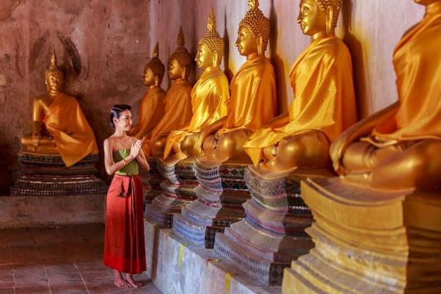 Belle ragazze tailandesi in costume tradizionale tailandese che prega statua di buddha a ayutthaya