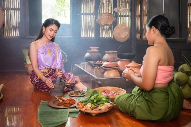 Una bella donna thailandese e indossa costumi tradizionali thailandesi, sia padroni che servi. sono seduti e cucinano in cucina. concetto di vita nel passato del popolo ayutthaya