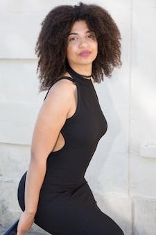 Bella donna magra in un abito nero con una scollatura nella parte posteriore