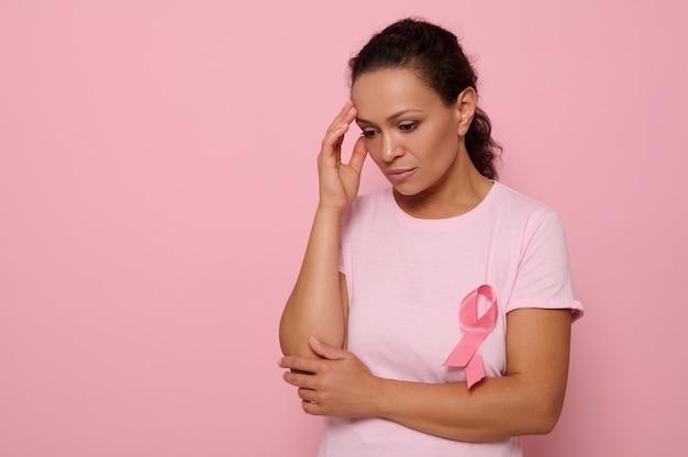 Bella donna premurosa in maglietta rosa con nastro rosa che guarda dall'alto in basso su sfondo rosa, mani sul tempio. giornata mondiale internazionale per la sensibilizzazione sul cancro al seno, concetto educativo, medico, spazio copia
