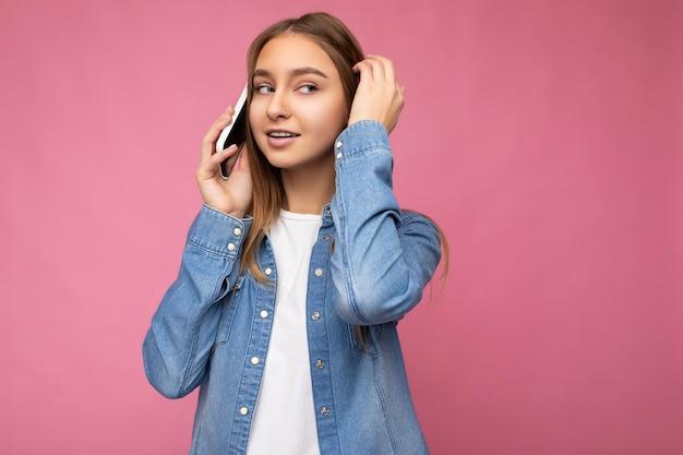 Bella giovane donna bionda premurosa che indossa camicia di jeans blu casual isolata su pink