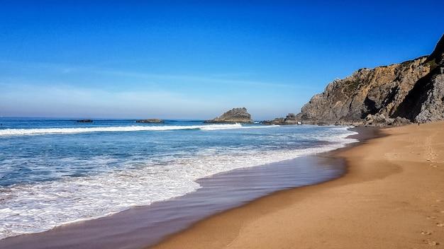 Bella marea dell'oceano vicino alle montagne