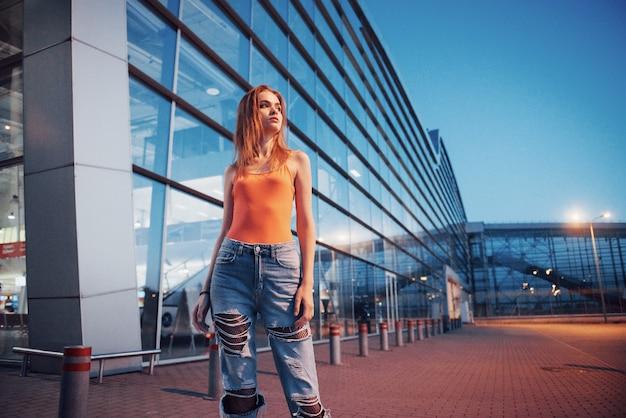 Bella ragazza turistica che cammina in una strada trafficata della città vicino all'aeroporto. donna che guarda la fotocamera all'aperto indossando la maglietta rossa alla moda.