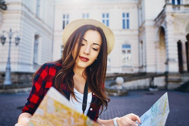 Bella ragazza turistica con capelli castani che indossa cappello e camicia rossa, che tiene la mappa al vecchio fondo della città europea e sorridente, viaggiando.