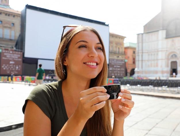 Bella donna turistica beve caffè italiano all'aperto. donna sorridente felice con la tazza di caffè sul paesaggio italiano soleggiato.