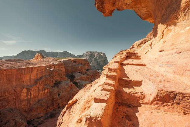 Un bellissimo sentiero che porta al cielo, scavato nelle rocce sabbiose nel deserto della città di petra