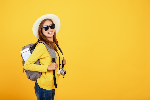 Donna asiatica del bello viaggiatore con la macchina fotografica su fondo giallo