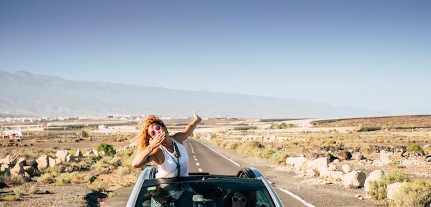 Bella giovane donna viaggiatrice manda un bacio stando fuori dal tetto di un'auto decappottabile mentre la sua amica guida per i viaggi e le vacanze in campagna