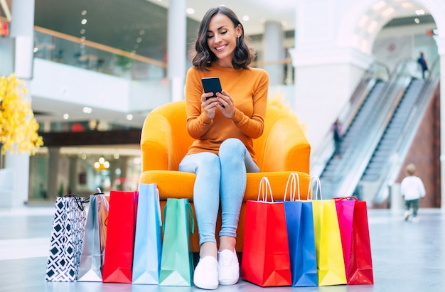 Bella giovane donna alla moda con molte borse della spesa colorate di buon umore con smart phone e carta di credito mentre era seduto nel centro commerciale durante il venerdì nero