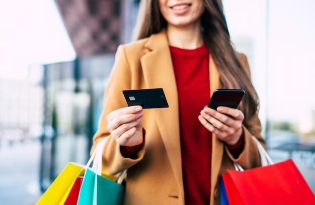 Bella giovane donna alla moda con molte borse della spesa colorate di buon umore con smart phone e carta di credito mentre si cammina nel centro commerciale durante il venerdì nero