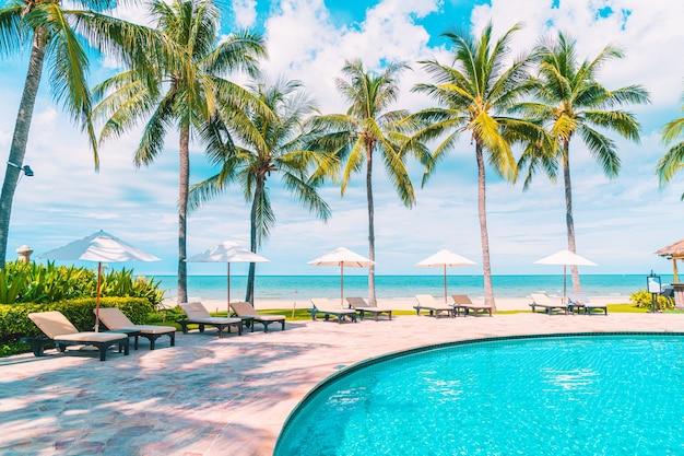 Bella spiaggia tropicale e mare con ombrellone e sdraio intorno alla piscina in hotel resort per viaggi e vacanze