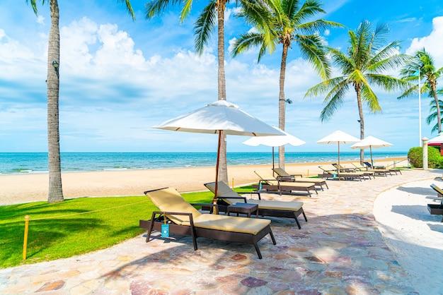 Bellissima spiaggia tropicale e mare con ombrellone e sedia intorno alla piscina in hotel resort per viaggi e vacanze