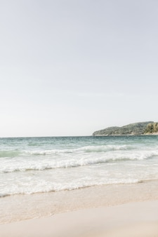 Bella vista sulla spiaggia tropicale con sabbia bianca, mare blu con onde e isola verde all'orizzonte di phuket