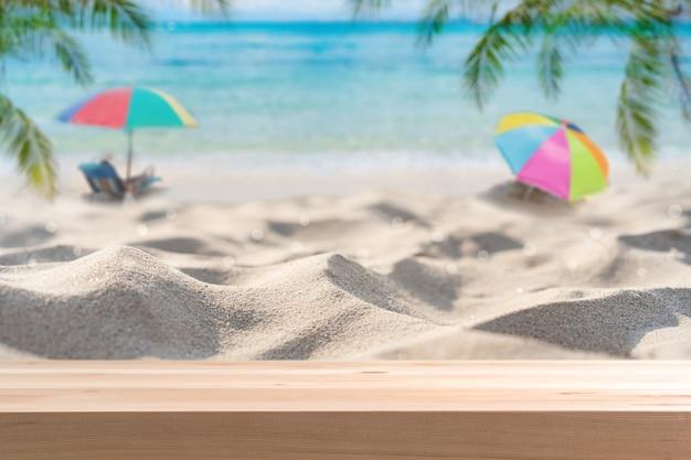 Bellissima spiaggia di sabbia tropicale con tavolo in legno vuoto e spazio per le copie, concetto di vacanza estiva