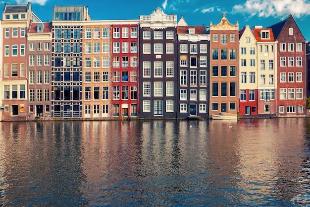 Belle tipiche case danzanti olandesi presso il canale damrak di amsterdam in giornata di sole, olanda, paesi bassi.