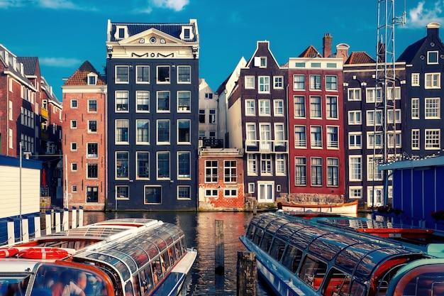 Belle tipiche case danzanti olandesi e imbarcazioni turistiche presso il canale damrak di amsterdam in giornata di sole, olanda, paesi bassi.