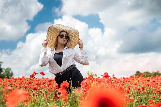 Bella signora ucraina da sola in cappello di paglia al campo di fiori di papaveri, sexy, giornata di sole