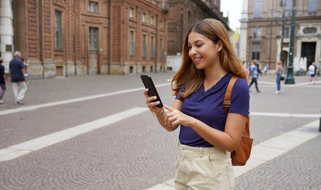 Bella studentessa universitaria che cammina in una strada cittadina digitando al telefono