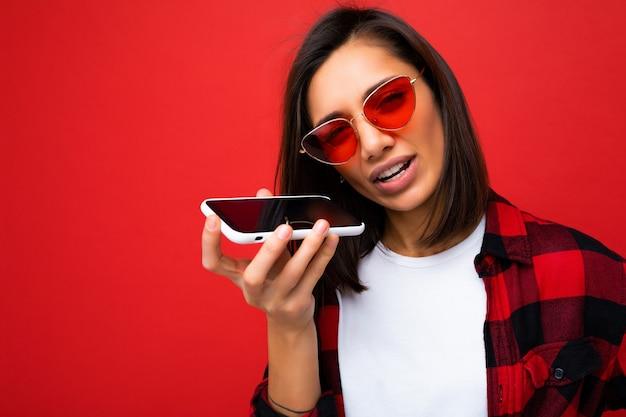 Bella giovane donna brunet sconvolta che indossa una camicia rossa elegante, una maglietta bianca e occhiali da sole rossi