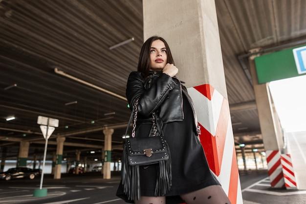 Bella donna urbana in giacca di pelle nera alla moda e vestito con borsa in pelle alla moda in un parcheggio in città
