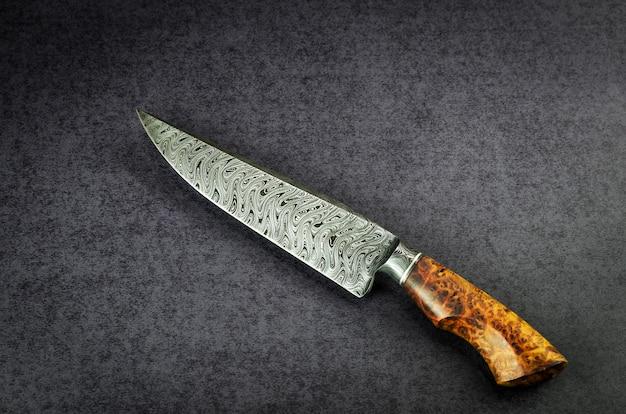 Bellissimo coltello multiuso in motivo damascato con manico in legno nobile su tavolo scuro